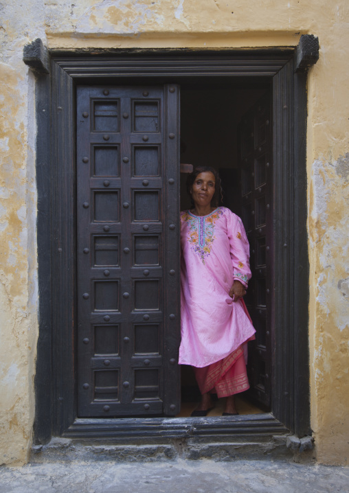 Woman standing in the frame of a wooden carved door, Lamu County, Lamu, Kenya