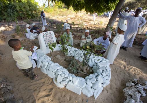 Tribute to shariff swaleh's grave on behalf of young boys during maulidi festival, Lamu, Kenya