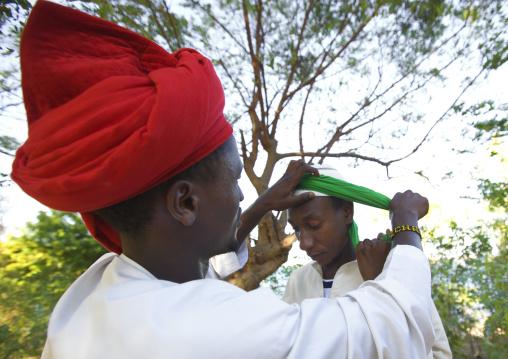 Red turbanned man putting white turban on another boy's head, Maulidi, Lamu, Kenya