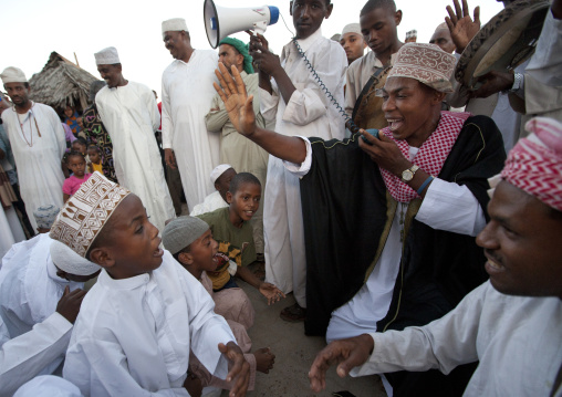 Praying and singing with young boys at maulidi festival celebration, Lamu, Kenya