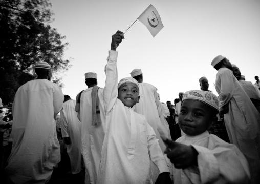 Child brandishing flag, Other boy showing during procession of maulidi lamu, Kenya