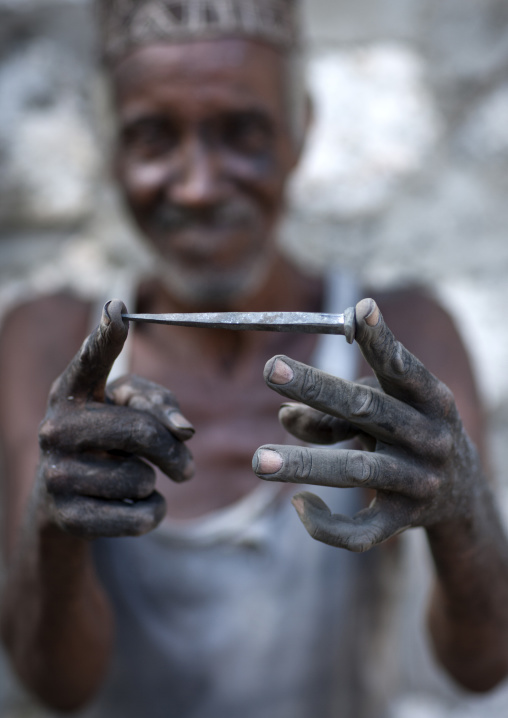 Blacksmith showing forged nail he made, Matondoni lamu, Kenya