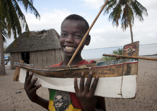 Young boy playing with a dhow boat model beach of lamu, Kenya