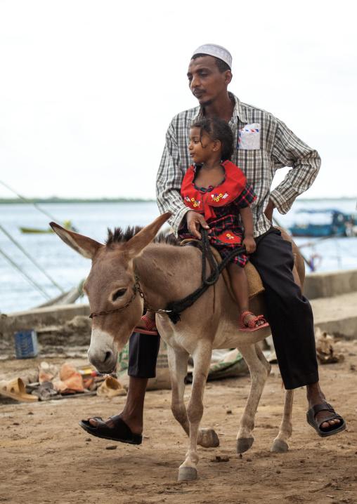 Man with his daughter riding a donkey in the street, Lamu County, Lamu, Kenya