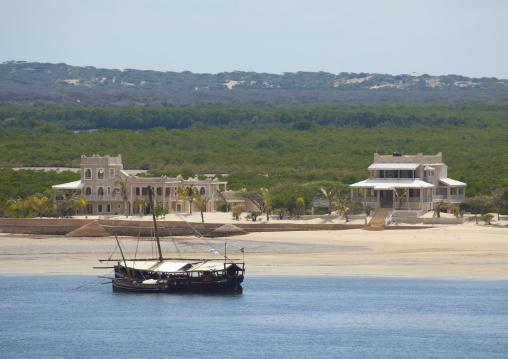 Dhow mooring along the beach in front of luxury villas, Lamu County, Manda island, Kenya