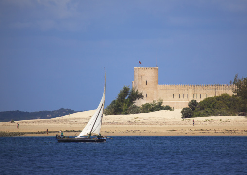 A dhow sailing along the coast, Fort hotel background, Shela, Lamu, Kenya