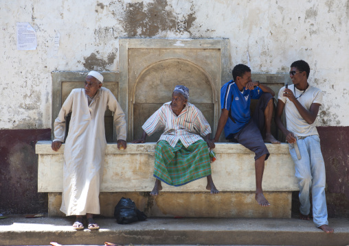 Group of people sitting on a fountain, Lamu county, Lamu, Kenya