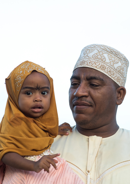 Sunni muslim father and daughter celebrating the maulidi festivities in the street, Lamu county, Lamu town, Kenya
