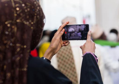 Sunni muslim woman taking pictures during the maulidi festivities in the street, Lamu county, Lamu town, Kenya