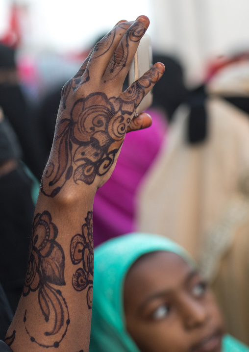 Sunni muslim woman with henna taking pictures during the maulidi festivities in the street, Lamu county, Lamu town, Kenya
