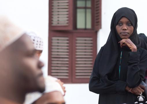 Muslim veiled young woman in the street during maulidi festivities, Lamu county, Lamu town, Kenya