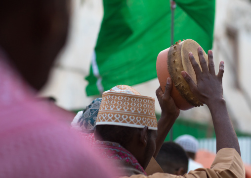 Sunni muslim men playing tambourines during the maulidi festivities in the street, Lamu county, Lamu town, Kenya