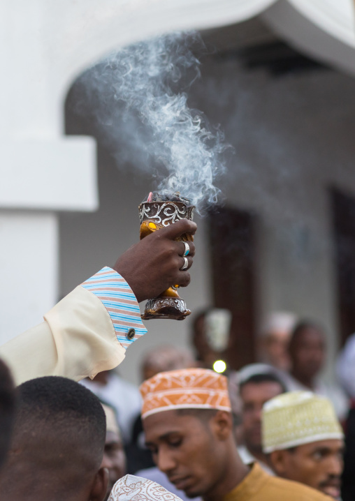 Sunni muslim man spreading insence with a censer during the maulidi festivities in the street, Lamu county, Lamu town, Kenya