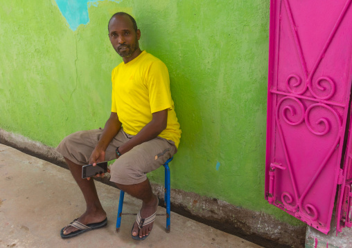 Kenyan man sit in the street in front of a colorful shop, Lamu county, Lamu town, Kenya