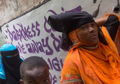 Mulsim people passing in front of a wall covered with graffitis, Lamu county, Lamu town, Kenya
