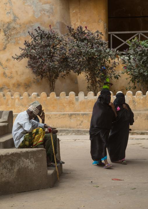 Muslim women in burqas passing in front of men sit on a bench in the street, Lamu county, Lamu town, Kenya