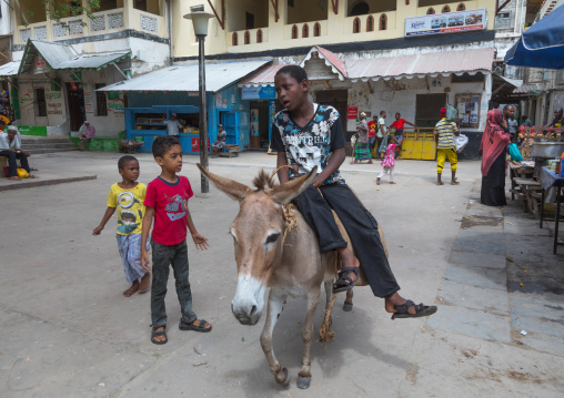Child riding a donkey on a square, Lamu county, Lamu town, Kenya