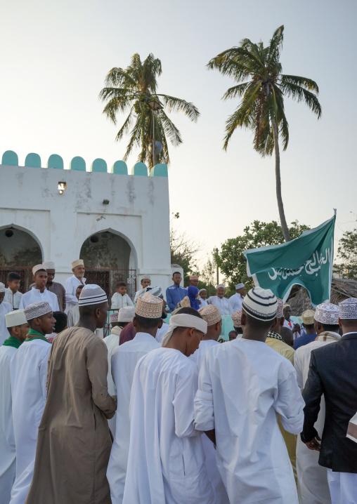 Sunni muslim people parading with flags during the maulidi festivities in the street, Lamu county, Lamu town, Kenya