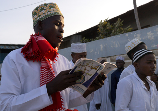 Sunni muslim man reading a religious book during the maulidi festivities in the street, Lamu county, Lamu town, Kenya