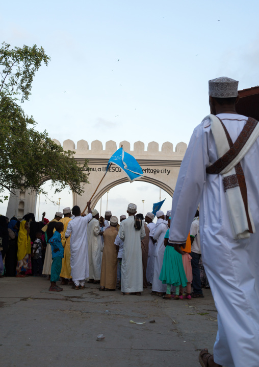 Sunni muslim people parading in front of the town gate during the maulidi festivities in the street, Lamu county, Lamu town, Kenya