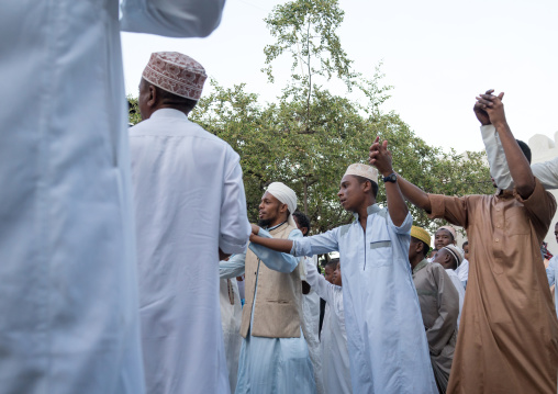 Sunni muslim men dancing during the maulidi festivities in the street, Lamu county, Lamu town, Kenya