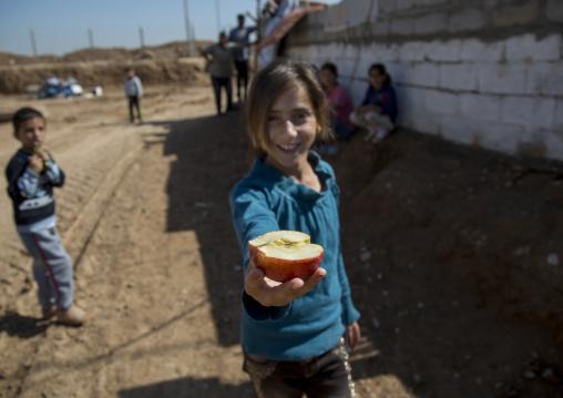 A Young Syrian Refugee Girl Sharing An Apple, Qushtapa Refugee Camp, Erbil, Kurdistan, Iraq