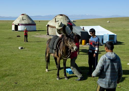 Man Helping A Bbc Reporter To Get On His Horse, Jaman Echki Jailoo Village, Song Kol Lake Area, Kyrgyzstan