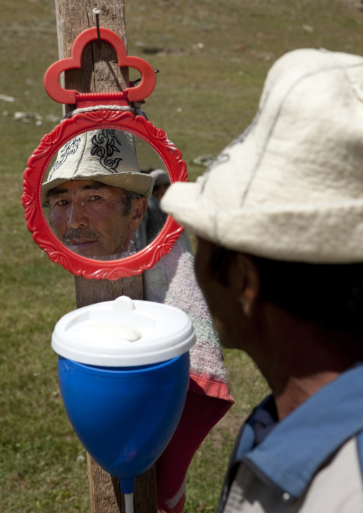 Man With Kalpak Hat Looking At Himself In A Mirror, Song Kol Lake Area, Kyrgyzstan