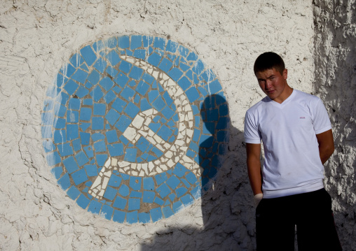 Young Man In Front Of A Mosaic Of The Hammer And Sickle, Kochkor, Kyrgyzstan