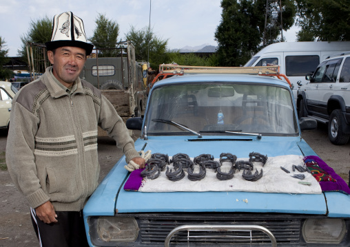 Man With Kalpak Hat Selling Horseshoes On His Car S Bonnet, Animal Market Of Kochkor, Kyrgyzstan