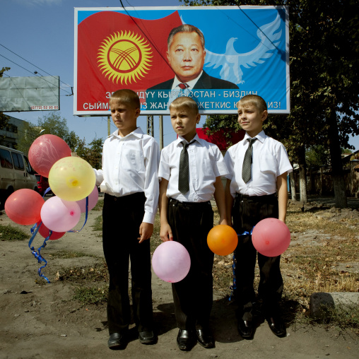 Boys In Suit Holding Balloons In Front Of  A Propaganda Billboard, Bishkek, Kyrgyztan