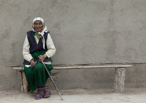 Old Veiled Woman Sitting On A Bench In Kochkor, Kyrgyzstan