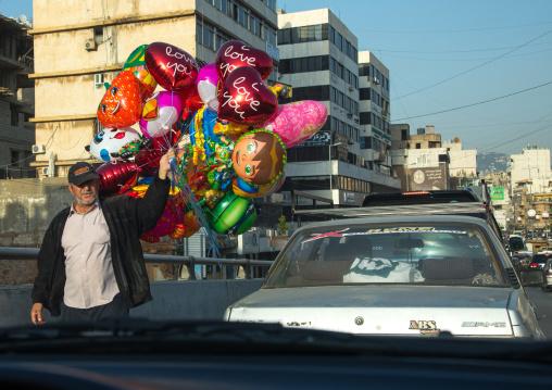 Syrian refugee man selling balloons in the street during traffic jam, Beirut Governorate, Beirut, Lebanon