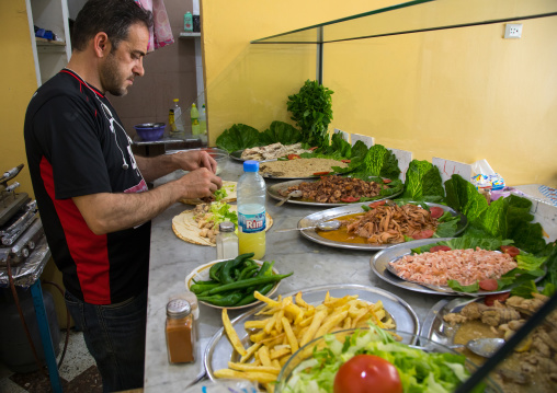 Lebanese man cooking fish in a local restaurant, North Governorate, Tripoli, Lebanon