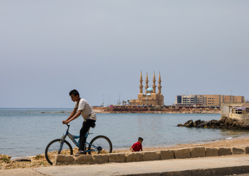 Child on a bicycle in front of corniche el Mina mosque, North Governorate, Tripoli, Lebanon