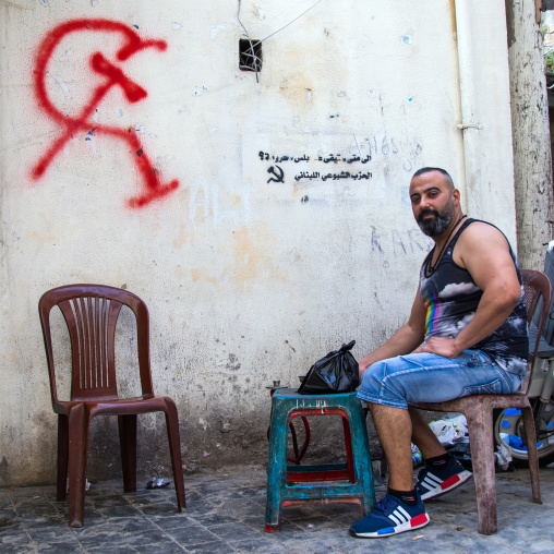 Lebanese man sit in the street in front of a communist party tag on a wall in el Mina, North Governorate, Tripoli, Lebanon