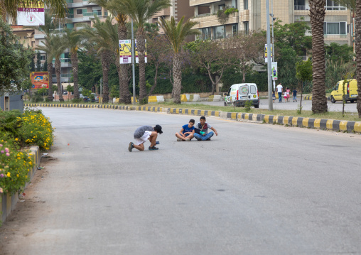 Syrian refugees children taking pictures in the middle of a road, North Governorate, Tripoli, Lebanon
