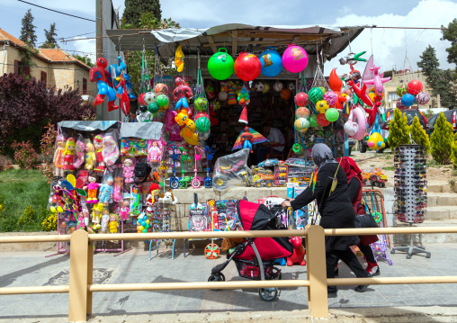 Lebanese woman with a baby-buggypassing in front of a toy shop with her child, Beqaa Governorate, Baalbek, Lebanon