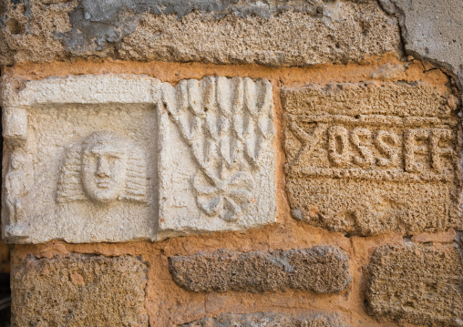 Carved stone at the entrance of a house decpicting the name and the face of the owner, South Governorate, Tyre, Lebanon