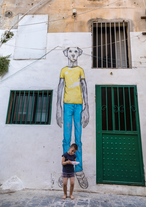 Lebanese kid standing in front of a giant dog painting in the street, South Governorate, Tyre, Lebanon
