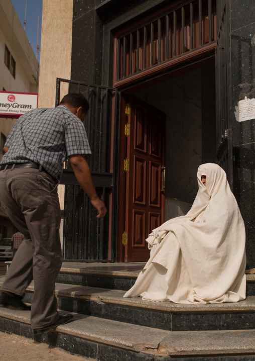 Woman begging on the street at the entrance of a shop, Cyrenaica, Benghazi, Libya
