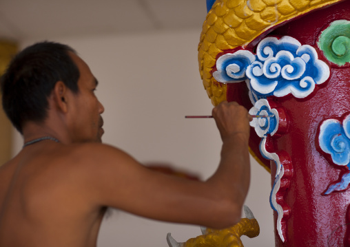 Man painting a pillar in a temple, Pakse, Laos