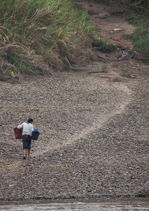 Khmu minority woman carrying water from mekong river, Xieng khouang, Laos