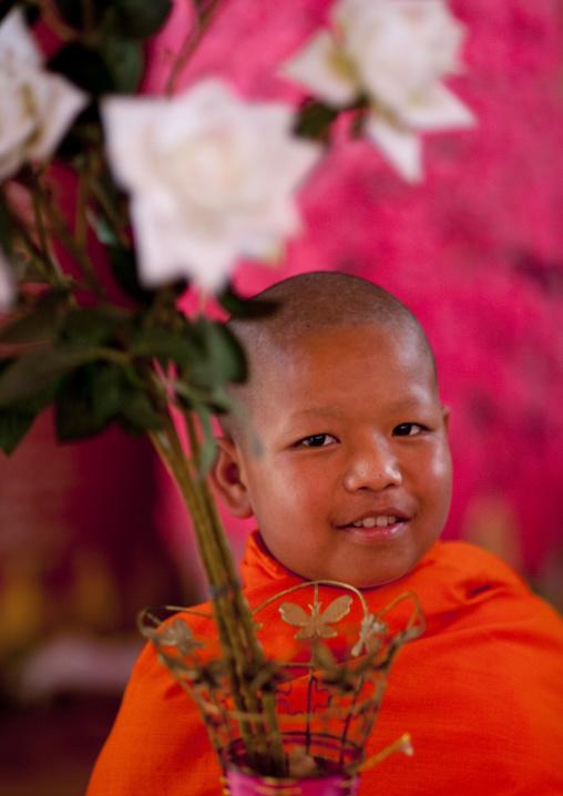 Novice buddhist monk with flowers, Nam deng, Laos