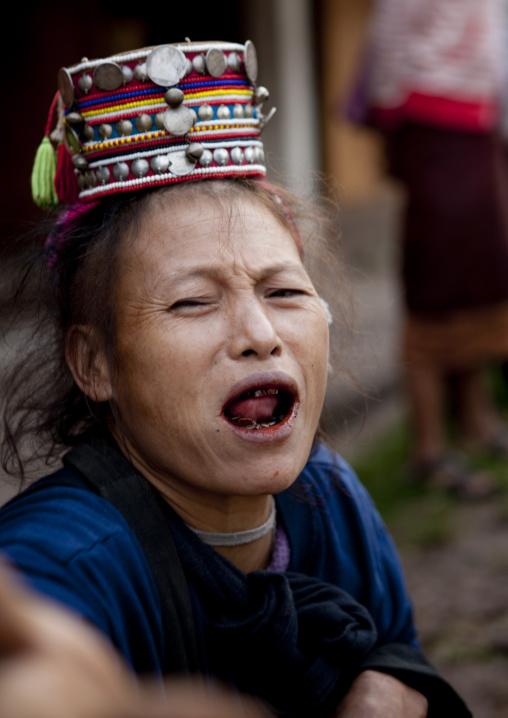 Akha minority woman with traditional headdress and black teeth, Muang sing, Laos
