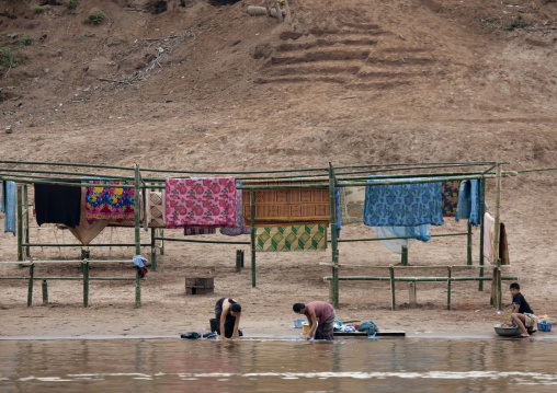 People washing clothes for lao new year on mekong river, Luang prabang, Laos