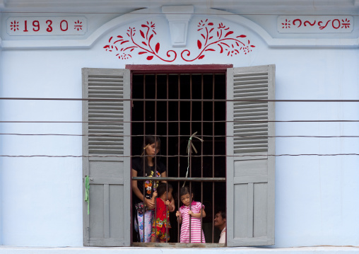 Family looking from a window, Luang prabang, Laos