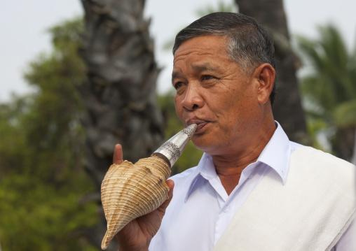 Man blowing in shell  during pii mai lao new year celebration, Luang prabang, Laos