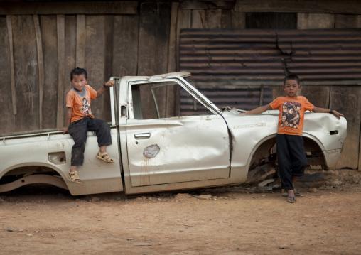 Hmong minority kids sitting on an ld car, Luang prabang, Laos
