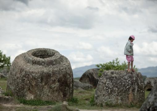 Tourist standing on a jar, Plain of jars, Phonsavan, Laos